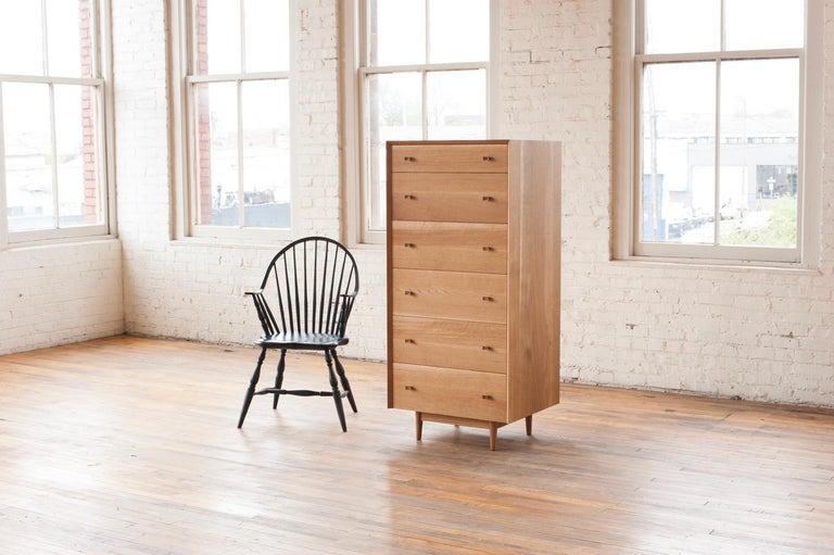 Phloem Studio Leo highboy solid white oak tall chest of drawers. The hardwood case has a grain matched waterfall miter from side to top to side. 6 solid maple wood drawers slide easily with self-closing slides. The knobs are turned on a lathe and
