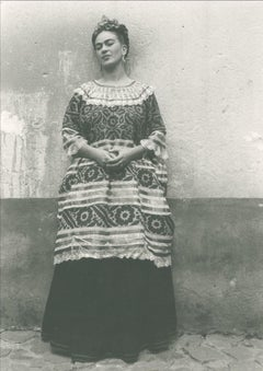 Untitled (Frida Kahlo standing against concrete wall)