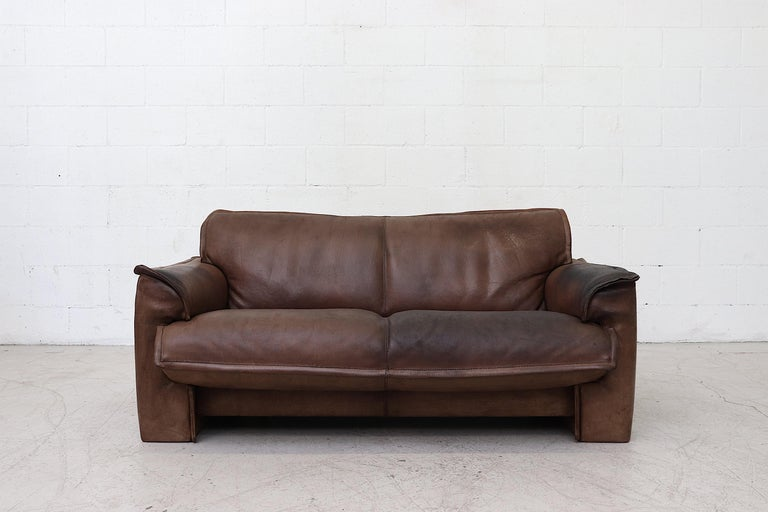 Dark Leolux buffalo leather love seat sofa. Well worn in with heavy patina and visible signs of wear. Other similar sofas available. Listed separately. Actual color may vary slightly from photo.