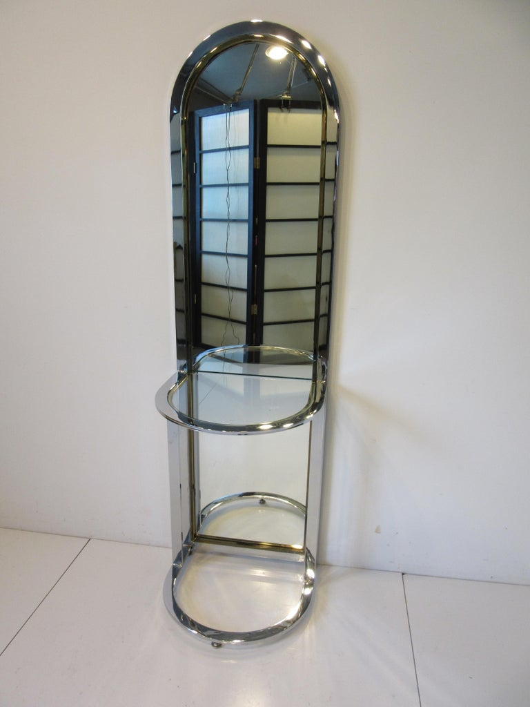 A arched topped standing Racetrack hall mirror in chromed steel having brass detailed accents with console glass shelve . A great design for an entrance way , end of hall or where you need a design statement , very well crafted and manufactured by