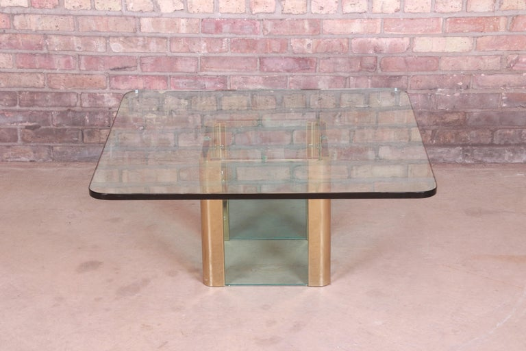 A gorgeous Mid-Century Modern Hollywood Regency brass and glass coffee or cocktail table  By Leon Rosen for Pace Collection  USA, circa 1970s  Measures: 35.75