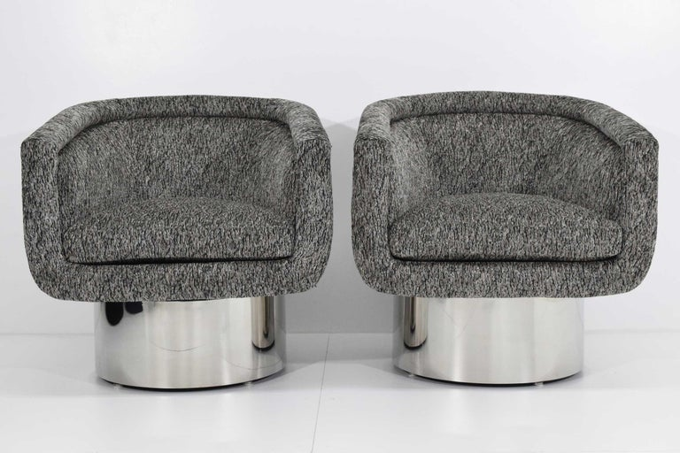Pair of handsome tub chairs on steel clad round swivel pedestal base by Leon Rosen for Pace Collection. Swivel is self correcting. These have new upholstery on them by Romo Black.