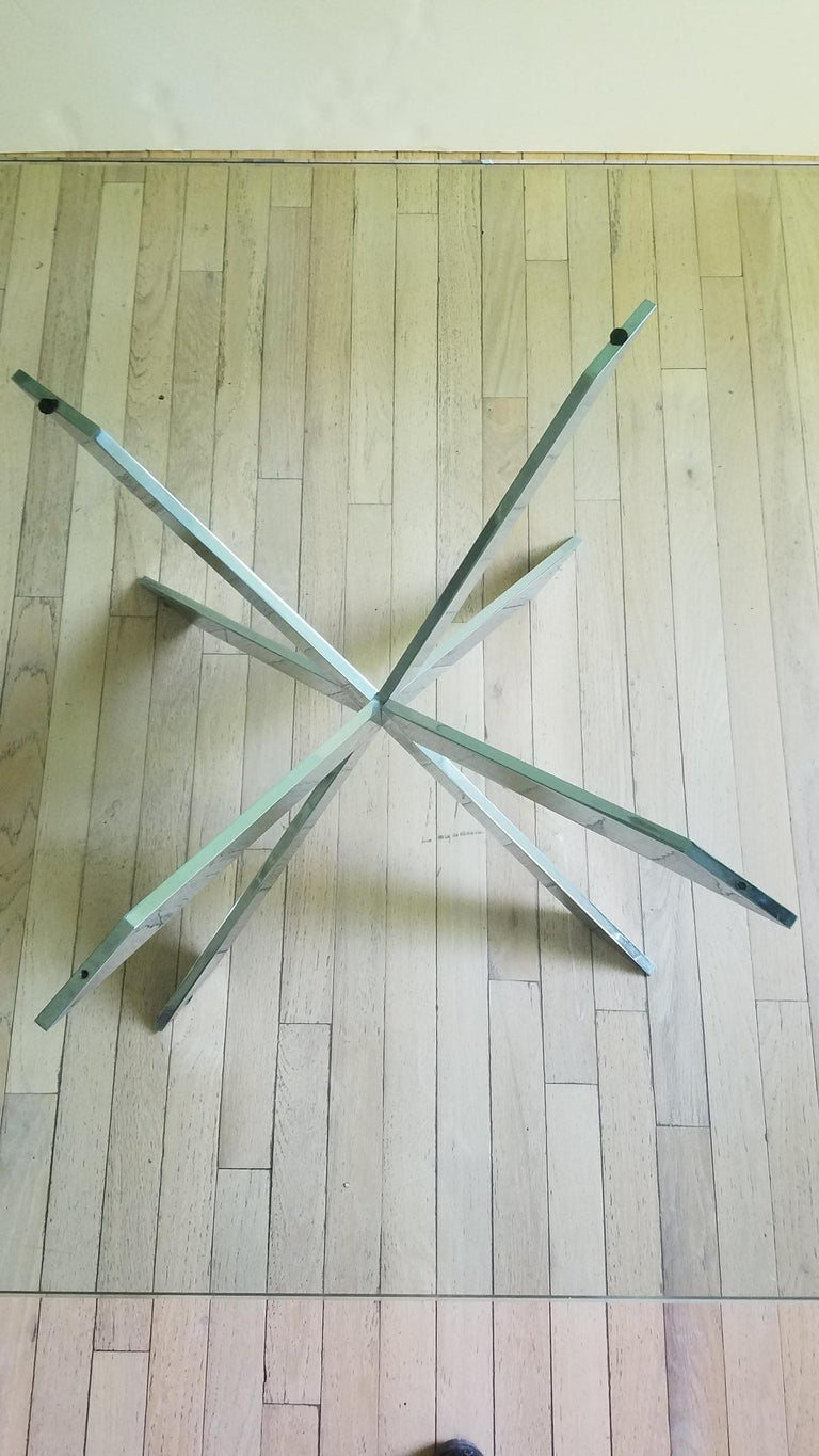 This iconic double X-base glass-topped cocktail table was designed by Leon Rosen for the Pace Furniture Collection in the 1970s. The base of intersecting X-forms is of chromed steel.  Leon Rosen designed many iconic pieces for the Pace Furniture