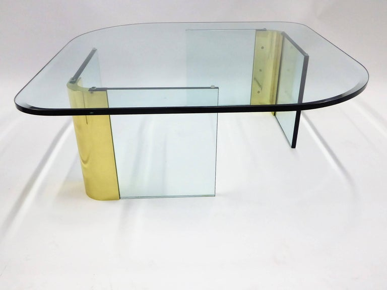 Fantastic thick glass and brass coffee cocktail table in the style of and attributed to Leon Rosen and the Pace Collection. The 3/4 inch glass top with a 1 inch bevel, in a rhomboid shape resting on two sets of glass legs with heavy brass corners.
