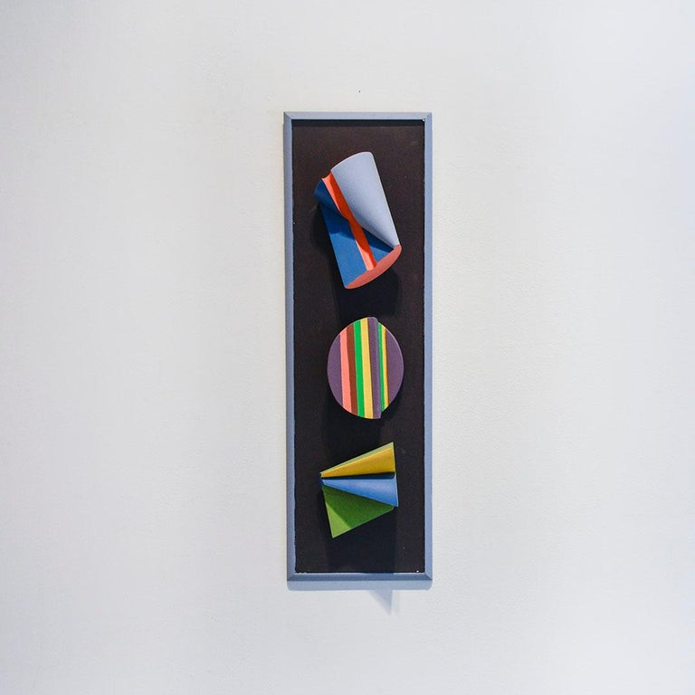 Abstract geometric three dimensional wall sculpture in black, blue, purple and green, with accents of yellow and pink