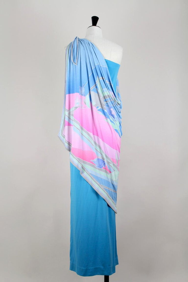 This fabulous 1970s Leonard one shoulder maxi dress is a find! It is constructed of a sleek maxi length dress that is cut from a french blue synthetic jersey and has a long side hem vent.  Attached to that dress at the shoulder is a shawl made from