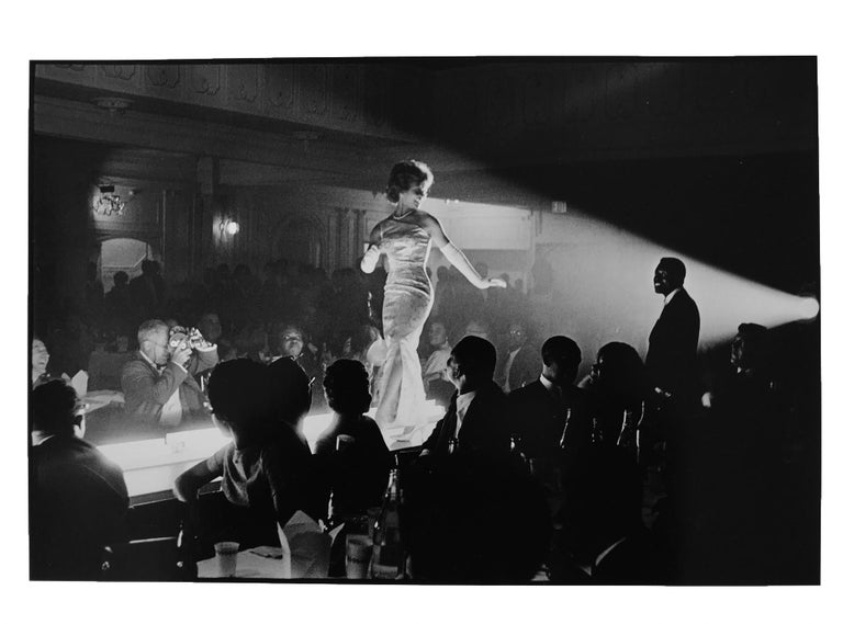 Fashion Show, 1963 by Leonard Freed, is a gelatin silver print from his famed Black in White America book (p.104).  Born in Brooklyn, New York, Leonard Freed worked as a freelance photographer from 1961 onwards. Magnum photographer Freed traveled