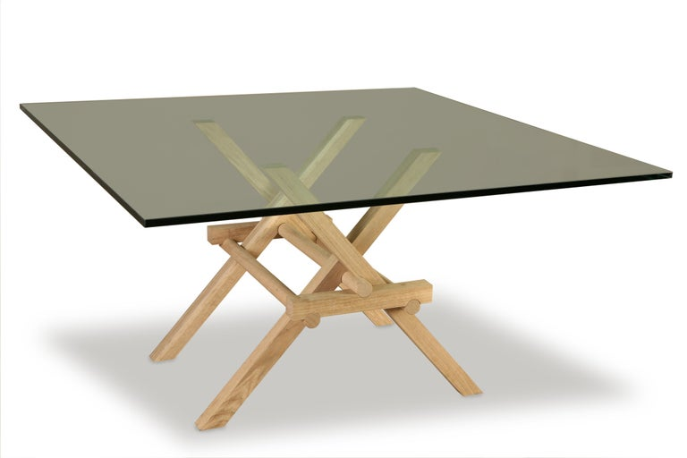 Leonardo contemporary table made of ashwood with interlocking legs, inspired by the construction of movable bridges by Leonardo da Vinci.  Glass top. Designed by Marco Ferreri