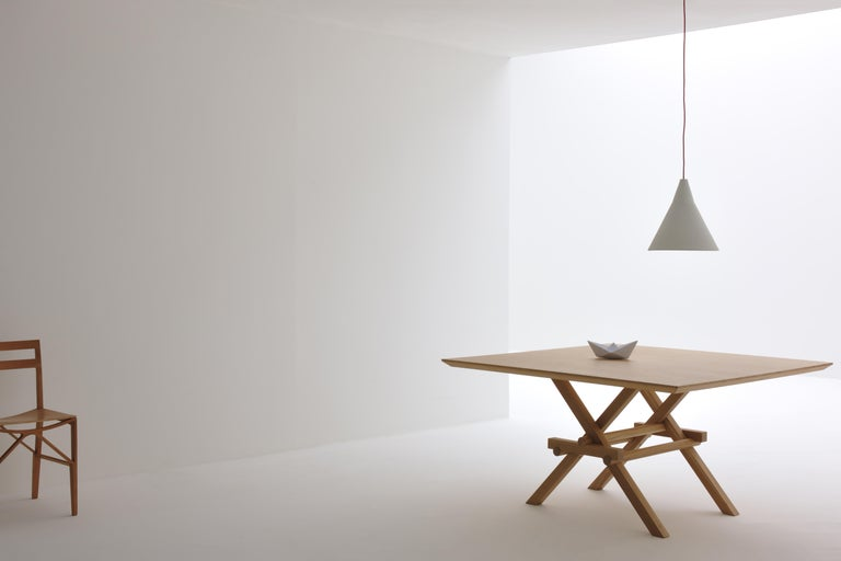 Leonardo contemporary table made of ashwood with interlocking legs, inspired by the construction of movable bridges by Leonardo da Vinci. Splay cut thin top. Designed by Marco Ferreri