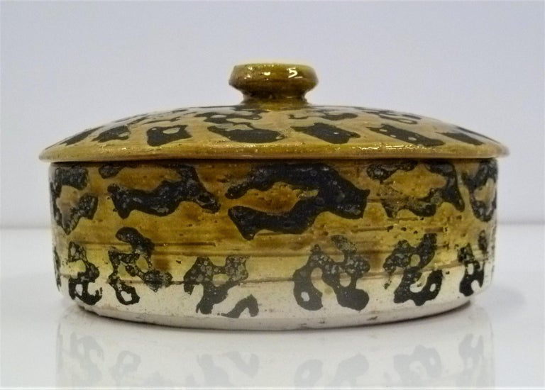 Exotic leopard motif Italian Mid-Century Modern covered pottery bowl from Rosenthal Netter. Probably designed by Alvino Bagni and by Bitossi, this hand painted leopard spots covered bowl has an intentional rough Brutalist feel to the touch. The