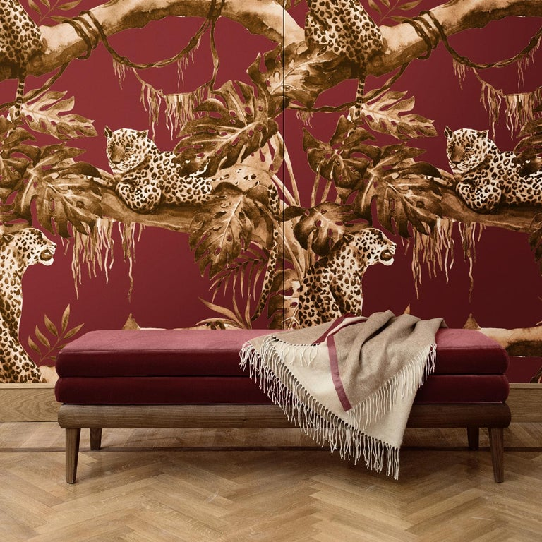 Stunning and unique, the design that adorns this wall covering is part of the Leopards Collection. Over a crimson-hued background, the scene of a leopard sitting under the shade of an exotic tree in golden tones adds a luxurious decoration in any