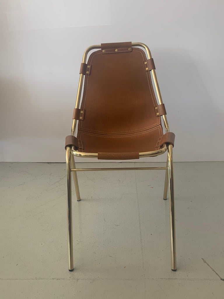 Newly produced dining room chair based off design of Charlotte Perriand Les Arcs chair Carmel leather with brass and contrast stitching Minimum of 6 per order.