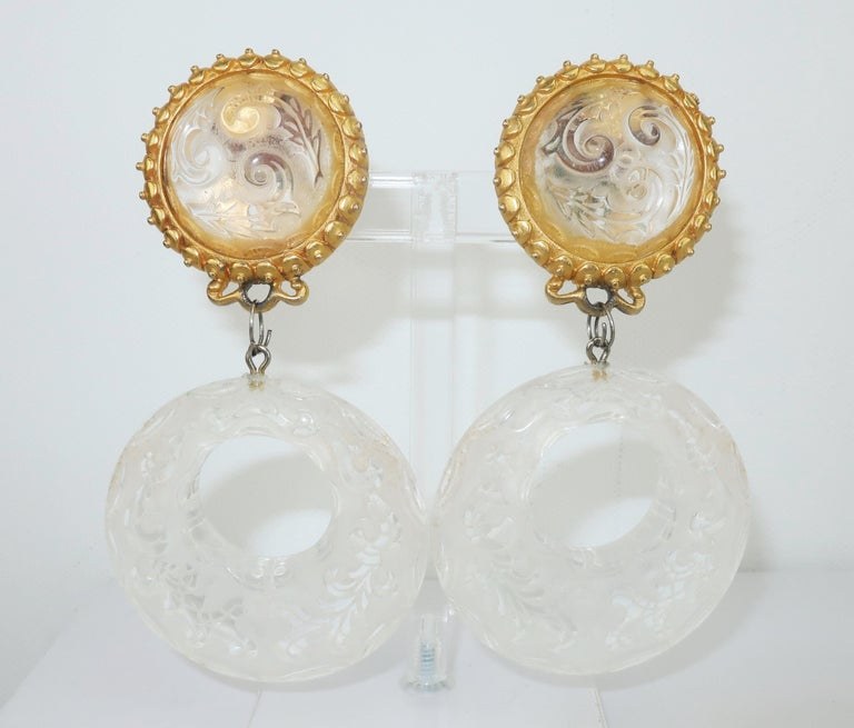 Leslie Block blends baroque opulence and 1980's glam with these carved lucite hoop dangle earrings.  The gold tone setting offers comfortable clip on hardware.  Signed at the back of one earring. CONDITION Overall good to fair condition with some