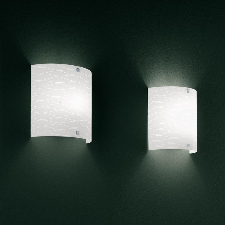 The class wall lamp was designed by Leucos design lab to be a fun, elegant lighting solution. The glass is hand-blown in Italy with a beautiful, wave-like horizontal etch detail. Compact overhang (ADA compliant). The class collection includes a