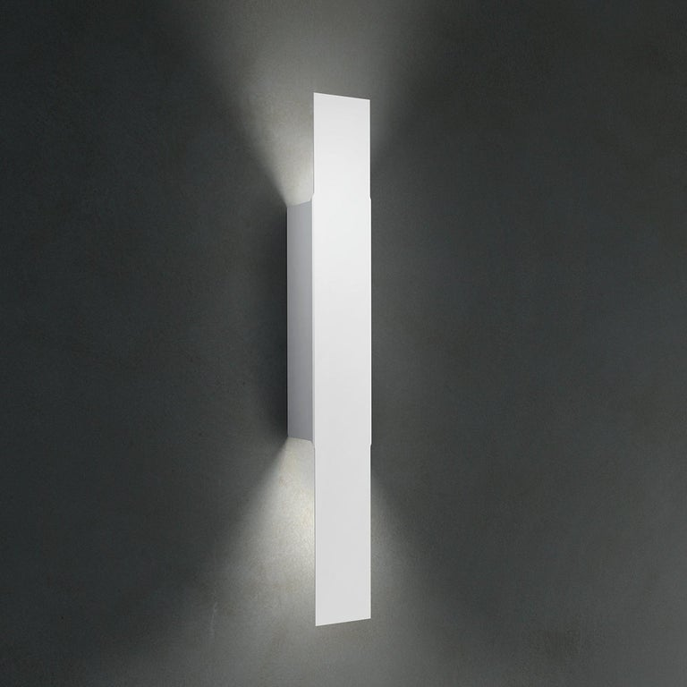 Opi is a sleek and architectural wall lamp made of metal twisted to create a compelling, asymmetric diffuser. It was designed in 2011 by Alessandro Piva to be a minimal yet effective wall lamp that is applicable to many contract or residential