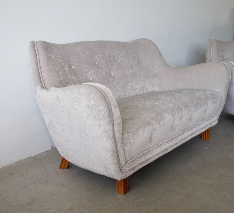 Two-seat button tufted sofa by Levy Carlssons Möbelafärr from circa 1952. Newly upholstered in shiny light beige/grey velvet. Lightly curved back. Legs made of stained beech.