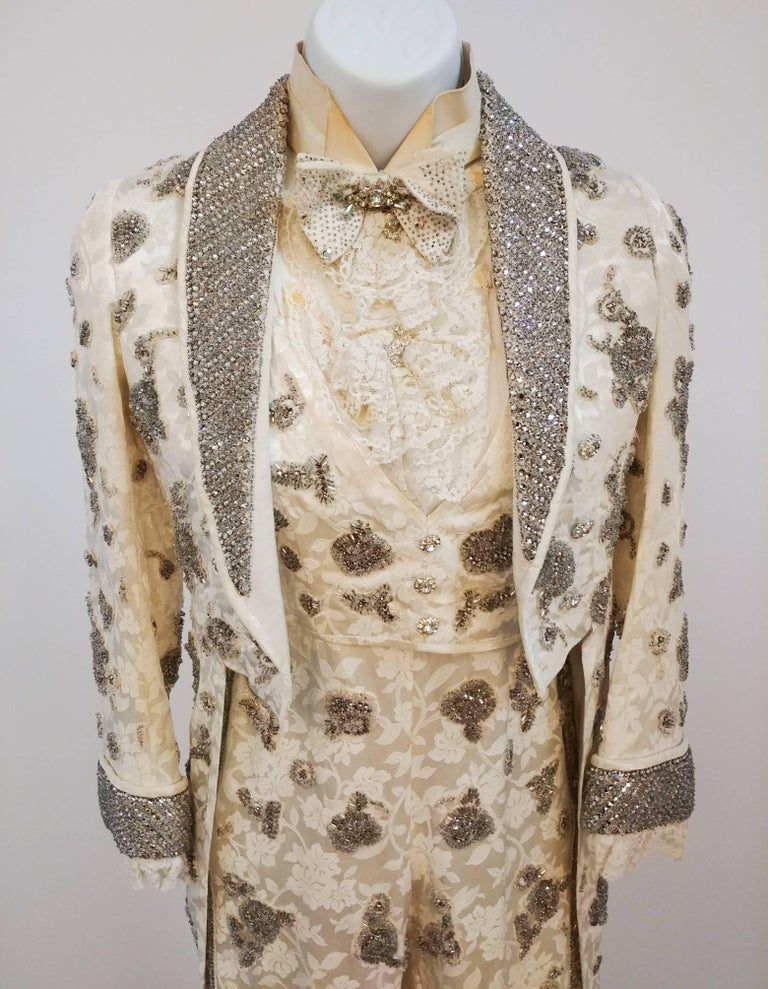 Rhinestone Bedazzled Miniature Tailcoat Set. Rhinestone-encrusted three-piece tailcoat set. Set consists of tailcoat, jumpsuit which zips up back, faux vest that buttons onto the waist of the jumpsuit, detachable jabot, paper collar, and bowtie.