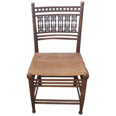 Liberty & Co. A Moorish Walnut Side Chair with Thebes Style Slung Leather Seat