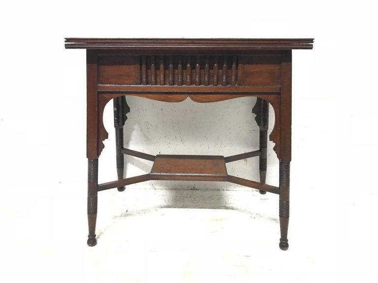 Liberty & Co. an Anglo-Moorish Arts & Crafts fold over card and games table in Walnut with green baize interior when open. Turned details to the upper and arched apron with turned and incised legs united by a cross stretcher. There is also an