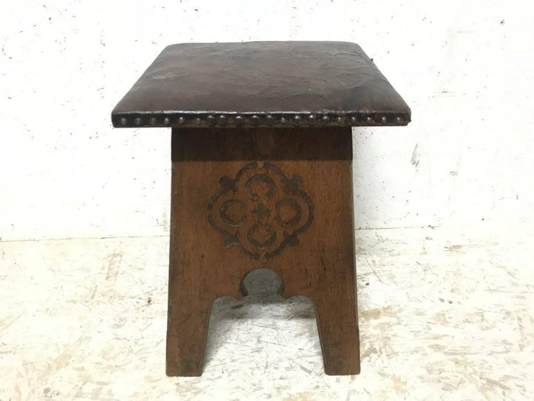 Liberty & Co., an Arts & Crafts oak stool with original embossed leather seat depicting flowers in bloom with stylized carved devices to all four sides and Moorish arched details.