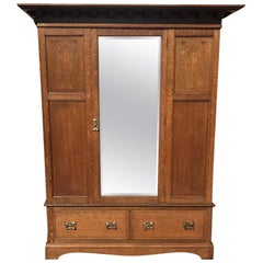 Liberty & Co, an Arts & Crafts Oak Double Wardrobe with Stylised Floral Inlays