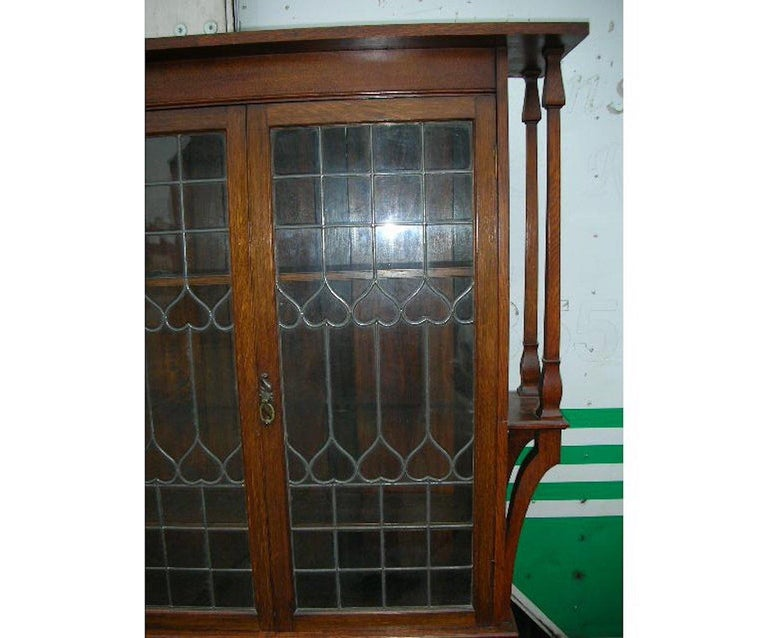 Arts and Crafts Liberty & Co. an Arts & Crafts Oak Glazed Bookcase with Stylized Heart Details For Sale