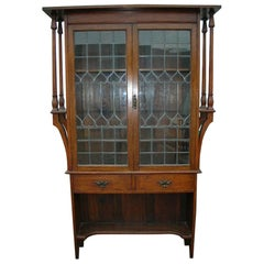 Liberty & Co. an Arts & Crafts Oak Glazed Bookcase with Stylized Heart Details