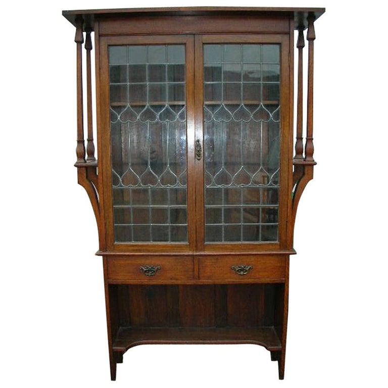 Liberty & Co. an Arts & Crafts Oak Glazed Bookcase with Stylized Heart Details For Sale