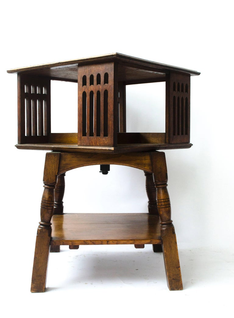 Liberty & Co. A rare Arts & Crafts oak revolving bookcase table on square and turned legs, united by a lower shelf.