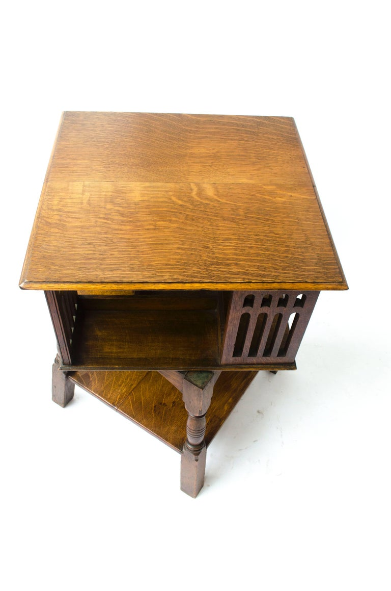 English Liberty & Co an Arts & Crafts Oak Revolving Bookcase Table on Square Turned Legs For Sale