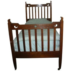 Liberty & Co. Attributed, an Arts & Crafts Oak Bed with Stylized Floral Cut-Outs