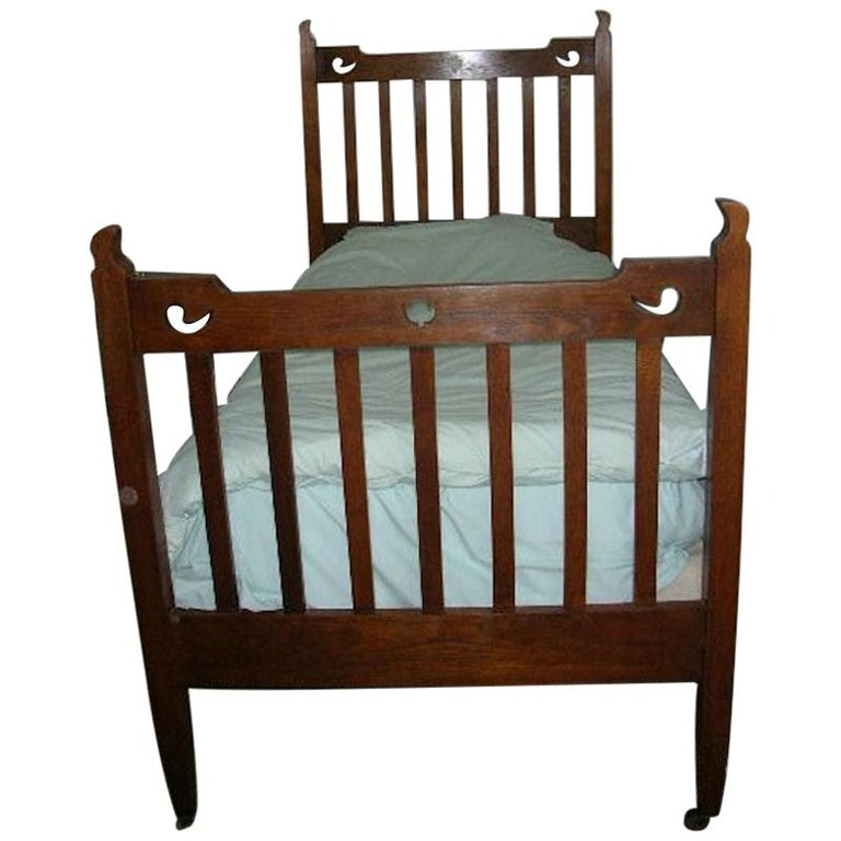 Liberty & Co. Attributed, an Arts & Crafts Oak Bed with Stylized Floral Cut-Outs For Sale