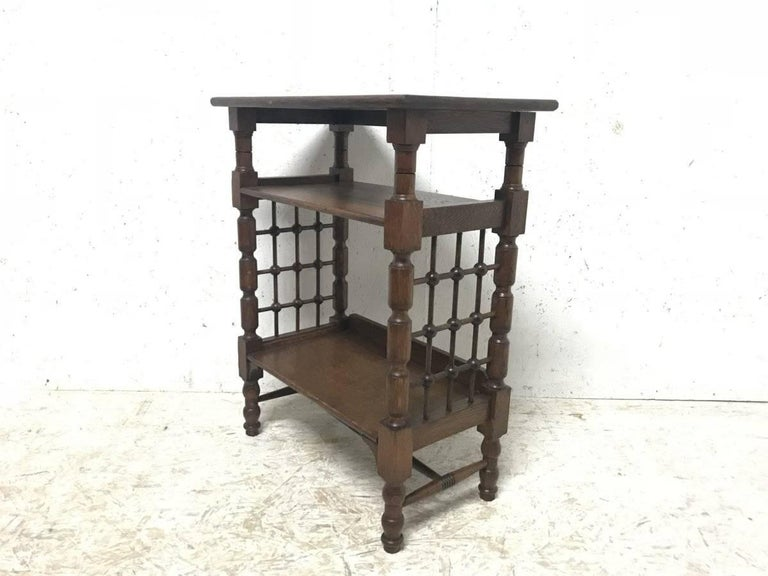 Liberty & Co. attributed. Made by William Birch. An Arts & Crafts three-tier book stand with Moorish turned lattice work decoration to the sides with turned legs united by a turned and incised H stretcher.