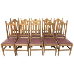 Liberty & Co, Ten Arts & Crafts Oak Dining Chairs with Stylised Floral Details