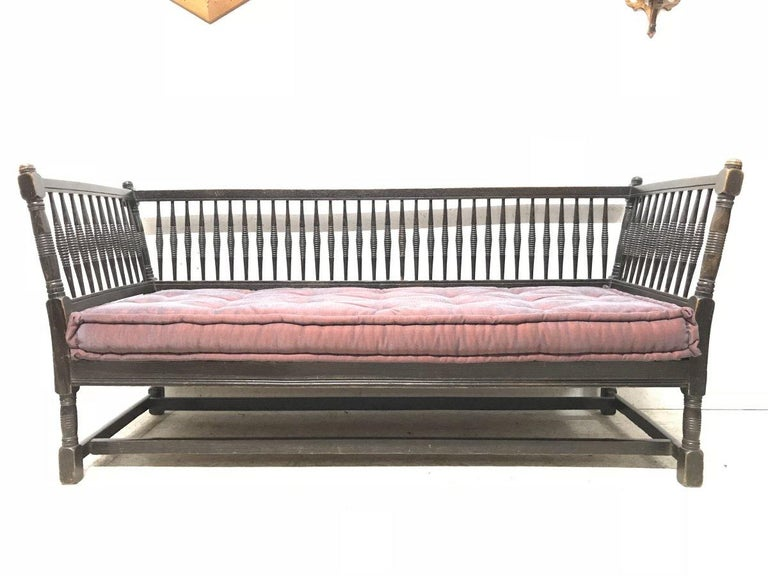 Liberty & Co, made by William Birch. An Arts & Crafts dark oak settee or sofa with turned finials, angular sides and turned uprights to the sides and to the back supports, square and turned legs united with twin stretchers below.