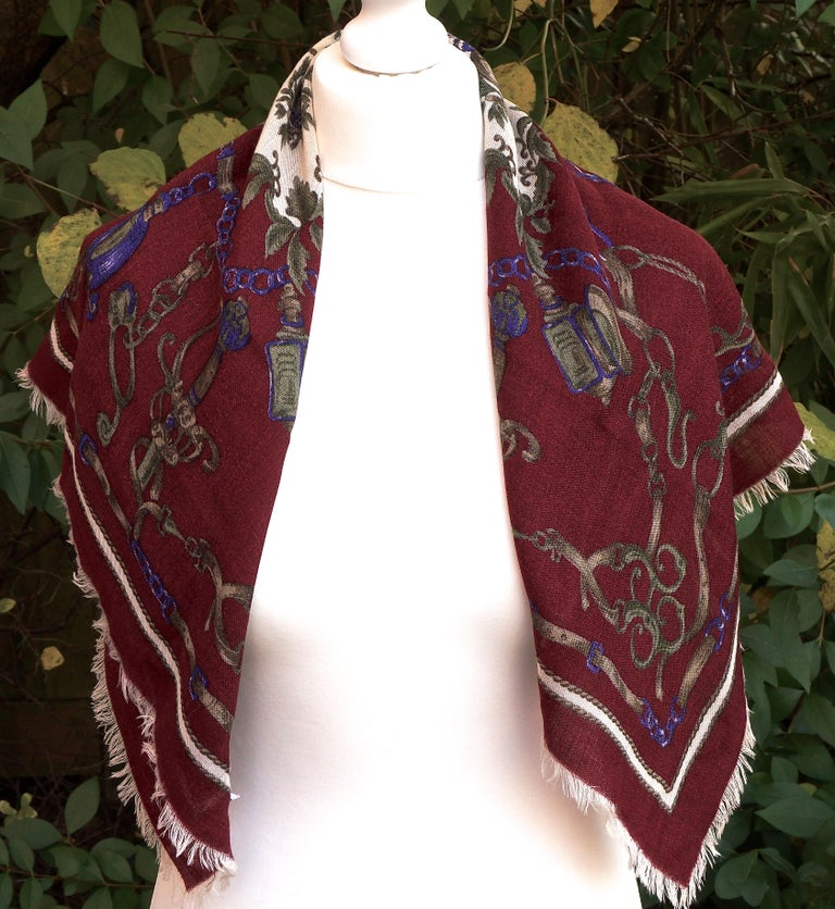 Square Liberty of London 100% wool scarf in blue, brown, green and cream, on a burgundy background. It features a lovely belt and chain print, with charms. The centre has a rope and tassel design. The edges are fringed,  and the scarf is made in