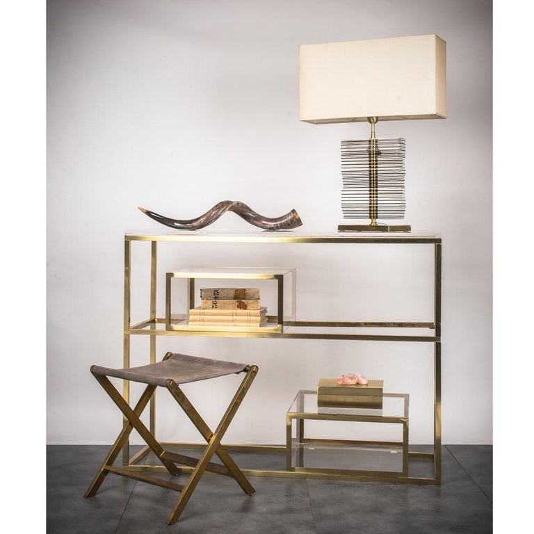 This elegant console features two transparent plexiglass shelves framed in a polished brass geometric structure and two plexiglass movable boxes that can be positioned as pleased. This piece is ideal for every type of interior, both by the walls and