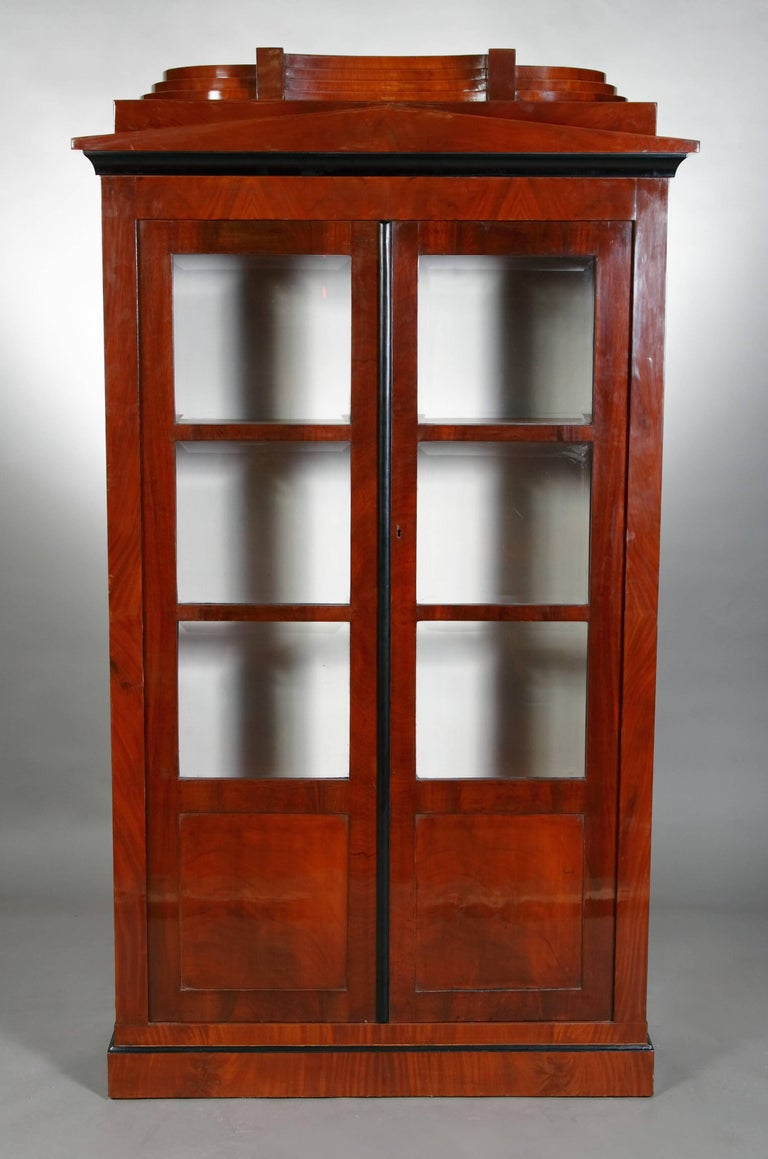 Pyramid mahogany on solid conifers, also back wall. On stepped frame base, high-corpuscular body. The front has two triple-sectioned, door-glazed, casted doors, the panels are handcrafted and facetted. Over cantilevered profile cornice flat gypsum,
