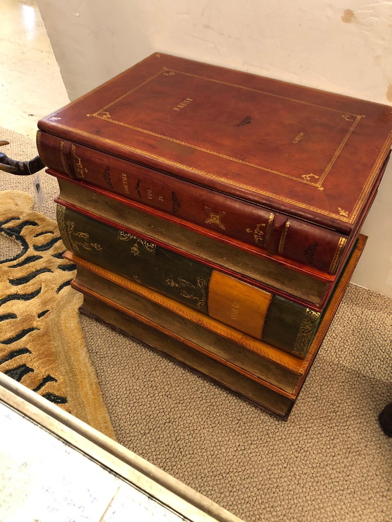 Stunning gilt and leather bound stacked book form table with lift up top revealing a storage compartment and single drawer. Green and white Italian papered interior.