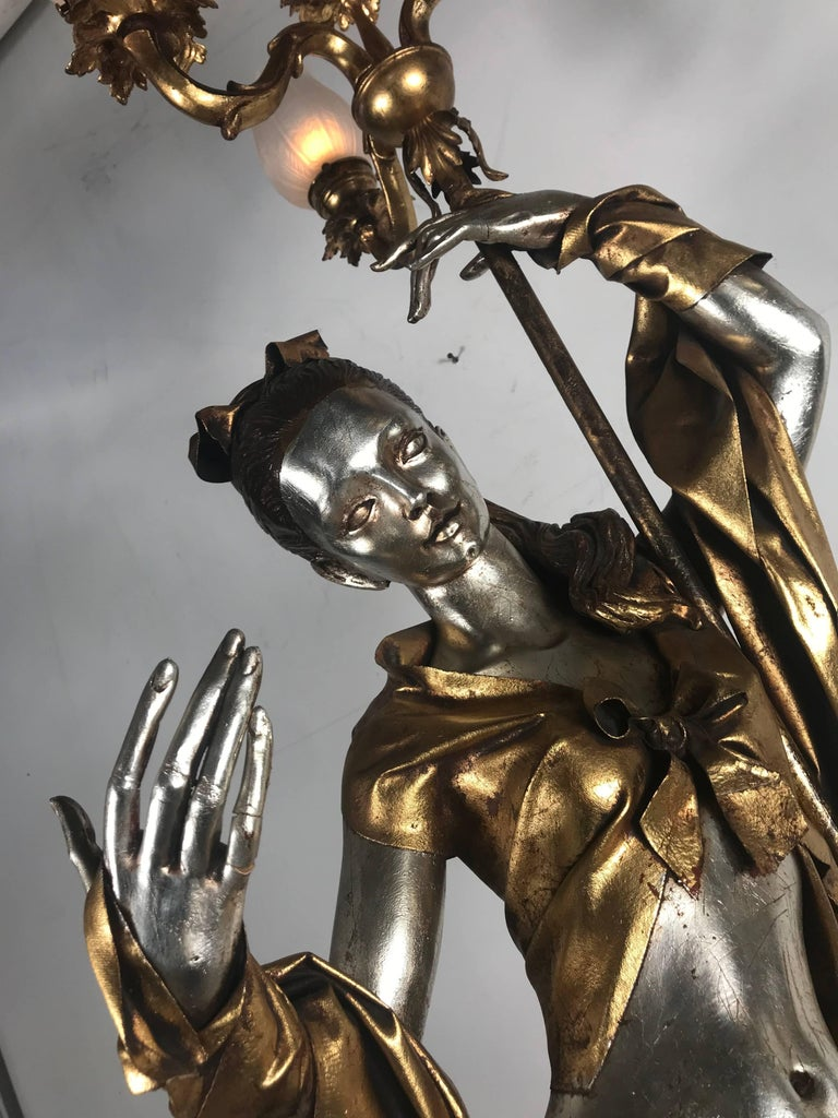 Life-like figural woman torchere floor lamp, gold and silver leaf by ARP. Stunning depiction of Romanesque woman figure holding five-light candelabra. Beautifully gilded in silver and gold. Wonderful details.