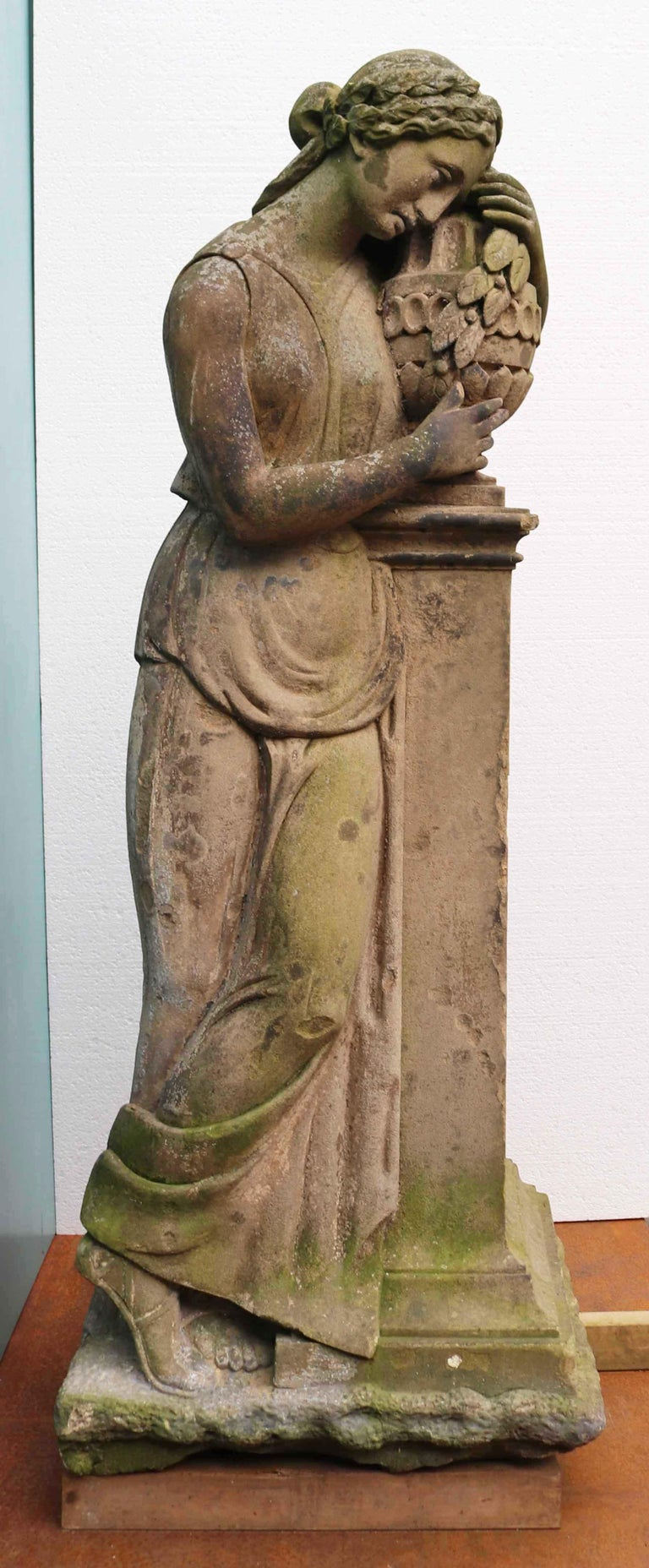 About  An impressive life-size hand carved natural stone statue of a woman in Classical Greek or Roman dress, grasping a vase.  Condition report  Good structural condition. No breaks or repairs. Weathered finish. Traces of old