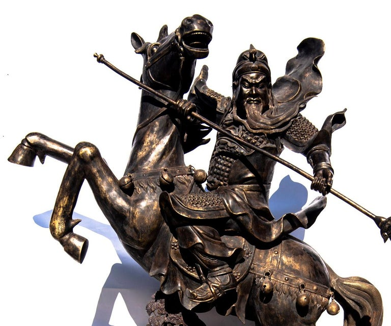 This life-size bronze with gold highlights of the Chinese General Guandi upon horseback brandishing his sword as his beard flies in the wind. The horse is resting upon the ground with bonzi like tree below the front hooves as he rears back in an