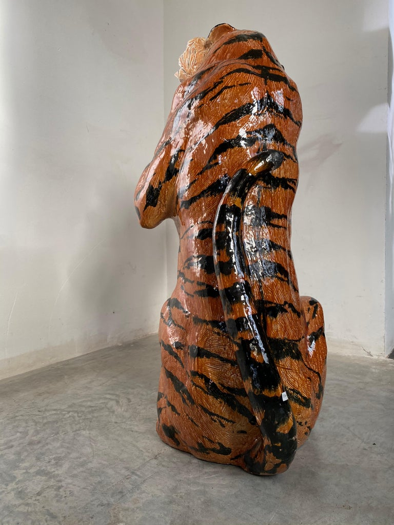 The stunning expression of a large and vibrant earthenware sculpture of a tiger, painted and glazed in white and orange-red with black markings, sitting snarling and resplendent with his teeth bared. Made in Italy, circa 1970s. Hand executed by a