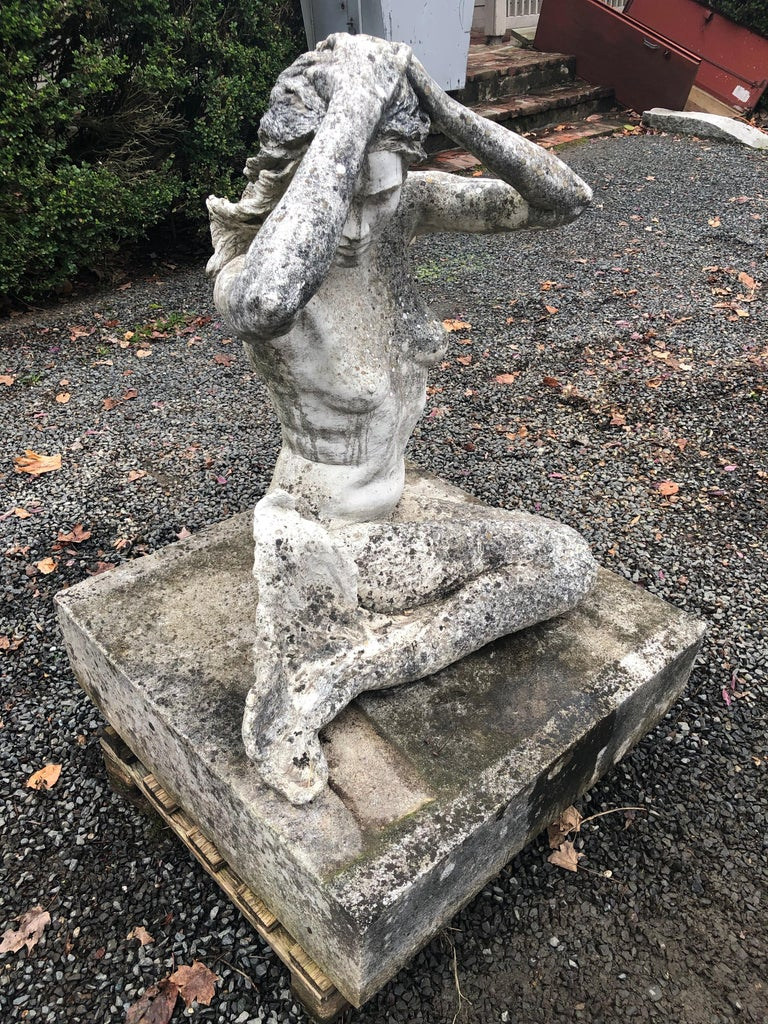 It's extremely rare to find good mermaid figures, and this one is a beauty. Her seated position with arms overhead and elegant scalloped fish-scales to her bottom half give this piece extraordinary look. Made of cast stone and with a beautiful