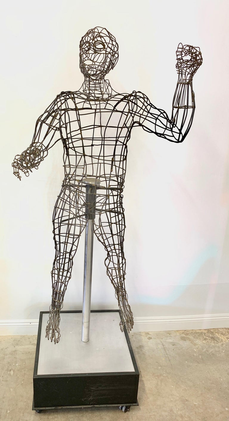 Massive wire sculpture of a man by Bruce Gray. Life-sized sculpture floating on rolling cube base. Measures: Just over 7 feet tall. Fantastic detail and presence. Excellent condition.