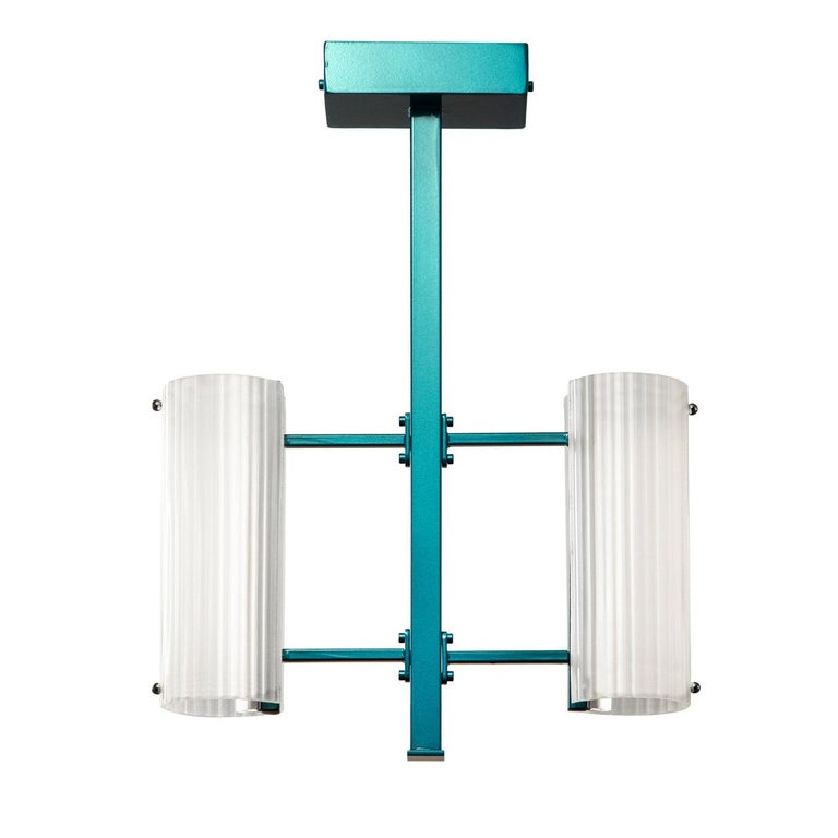 A striking pendant lamp that will add an accent of color to restrained, monochromatic interiors, this piece showcases a light blue metal frame sustaining two grooved cylindrical diffusers in white glass that host two LED strips (6W). A ballast of