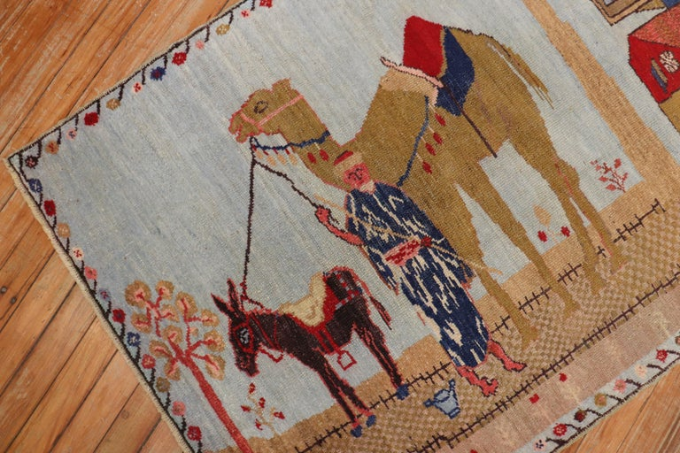 Mid-20th century Turkish pictorial rug woven in central turkey depicting a large camel and a small horse latched onto an older man with 2 trees and a house in the background  Size: 3' x 4'.