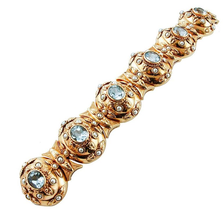 Beautiful retrò bracelet in 14 kt rose gold structure, mounted with light blue topazes and decorations of little pearls. This bracelet is totally handmade by Italian master goldsmiths. Topazes 21.30 ct , 10 mm x 8 mm Pearls 0.60 gr Total Weight