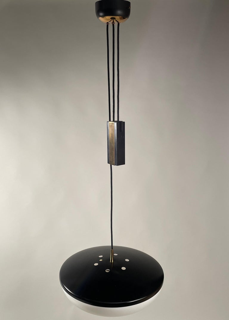 Black and polished brass structure with an adjustable hanging cord and counterweight, suspending a white plexiglass shade with a polished brass handle. Original sticker.
