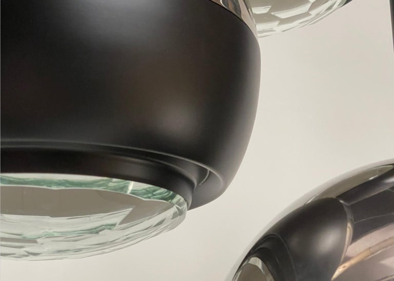 Three light fixture in chromed and black painted metal, with facetted glass discs at the bottoms.